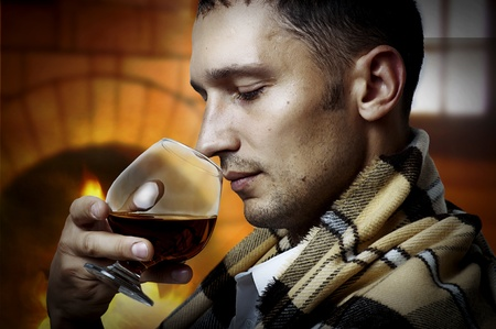 cognac: Taster. Young adult Man in tartan plaid holding in hand a glass of classy extra old brandy or cognac and smell it. He is inside home room siting about fireplace