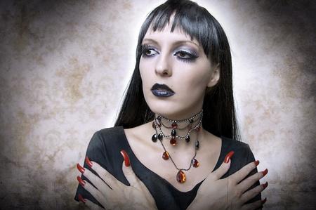 uñas largas: De Halloween concepto. Retrato de la moda vampiro noche de estilo gótico mujer o el mal witchin vestido negro y un collar vintage. Morena con el pelo de la salud a largo. Foto de archivo