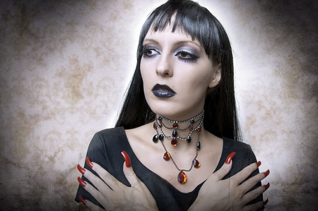 human fingernail: Halloween concept. Fashion portrait of gothic style woman night vampire or evil witchin black dress and vintage necklace. Brunette with long health hair.