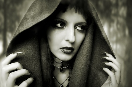 Halloween concept. Fashion portrait of witch or night vampire woman. Dark gothic makeup photo