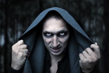 Portrait horrible fashion male vampire (demon or evil wizard) Halloween concept. Mystery white eyes Imagens