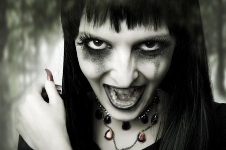 Halloween horror concept. Fashion portrait of witch or night vampire woman. Dark gothic makeup photo