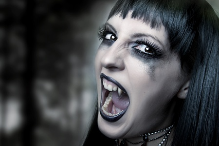 fangs: Halloween horror concept. Dark portrait of Night mystic woman vampire