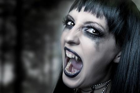 fangs: Halloween horror concept. Dark portrait of Night mystic woman vampire