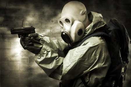post apocalypse: Post apocalypses world halloween concept. Portrair of man in gas mask with handgun Stock Photo