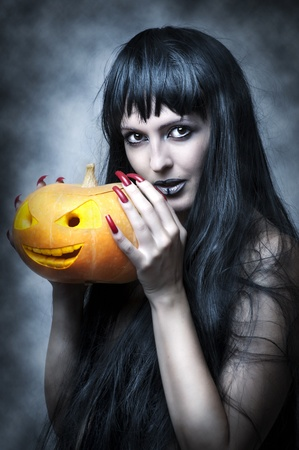 long shot: Halloween makeup. Sexy woman - Witch with long black hair and pumpkin smiling and look to shot