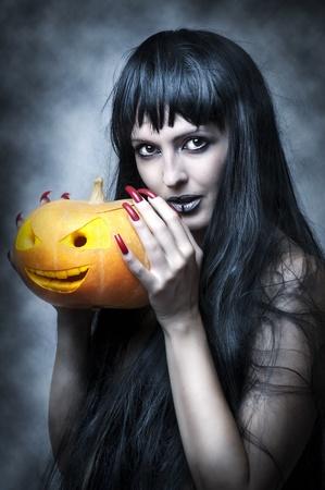 uñas largas: Maquillaje de Halloween. Mujer sexy - bruja con pelo largo y negro y calabaza sonriente y aspecto disparado