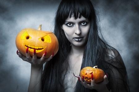 unas largas: Maquillaje de Halloween. Mujer sexy - Bruja con el pelo largo y negro y dos calabazas en las manos y mira sonriente a tiro