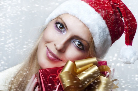 Christmas concept. Beauty portrait happy woman model holding gift in hands and smile  in santa claus hat
