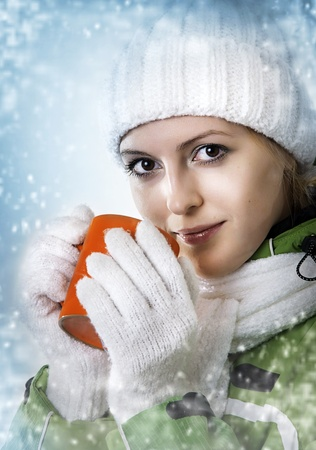 Winter. Young adult beautiful woman drink from orange cap. Snowflakes