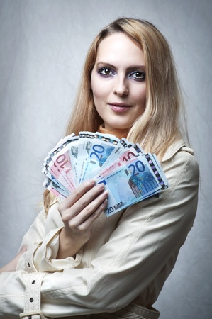 Portrait of smiling young woman holding money in the hand on gray background  Stock Photo - 10906146