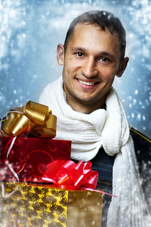 Young adult smiling caucasian handsome man with two christmas gift boxes in white scarf. Snow flakes Stock Photo - 10906150