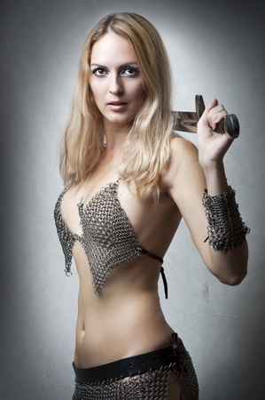 ancient warrior: Portrait of young sexy model. Woman warrior with sword in seductive armourlooking at camera. Joan of Arc Stock Photo