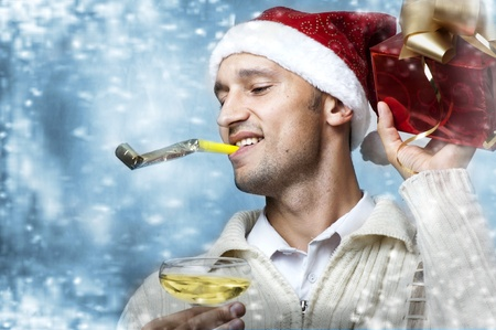 snow man party: Christmas party. Young adult smiling caucasian handsome man in santa claus hat with christmas gift box and glass of champagne. Snow flakes  Stock Photo