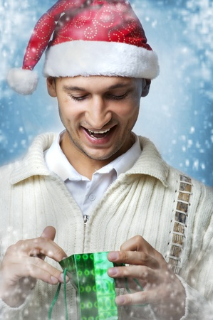 Young adult smiling wonder handsome man in santa claus hat with christmas gift bag. Snow flakes Stock Photo - 10941081
