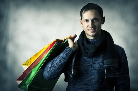 after shopping: Portrait of a young man wearing scarf and dark blue shirt after shopping with bags Stock Photo