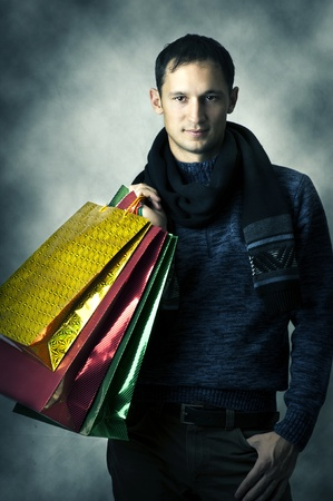 Portrait of a young man wearing scarf and dark blue shirt after shopping with bags photo