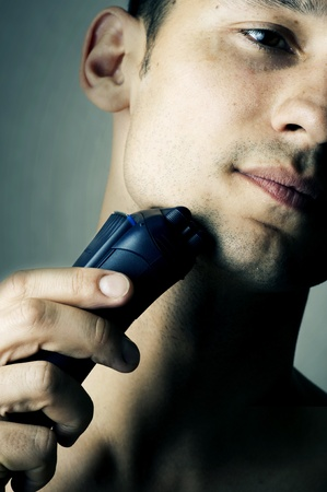 Fashion portrait of male chin and electric shaver. Focus on shaver Stock Photo