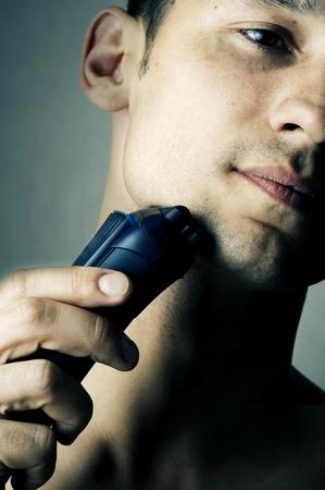electric shaver: Moda ritratto del mento maschile e rasoio elettrico. Focus su rasoio