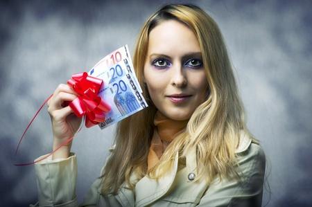 christmas profits: Fashion portrait of young beautiful woman winner holding money - 50 (fifty) euro.
