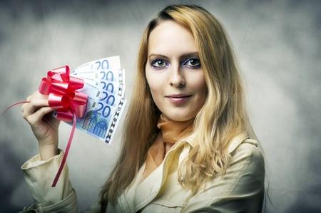 Fashion portrait of young beautiful woman winner holding money - 100 (one hundred) euro. Stock Photo - 11015476