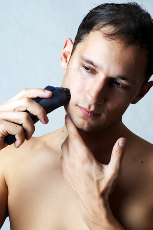 Fashion portrait of man shaving chin and cheek by electric shaver. Male hygiene photo