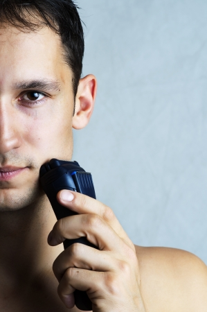 Fashion portrait of man shaving chin and cheek by electric shaver. Male hygiene. Copy space for your text photo