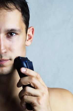 hombre afeitandose: Retrato de la moda ment�n y la mejilla del hombre afeitado por m�quina de afeitar el�ctrica. La higiene masculina. Copia espacio para el texto Foto de archivo