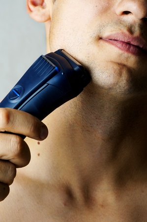 shaver: Fashion portrait of male chin and electric shaver. Focus on shaver Stock Photo