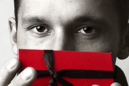 birthday present: Portrait of young pretty man holding red christmas gift box in hand. Male model eyes closeup