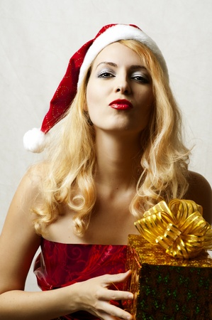 Fashion portrait of sexy blond woman in red santa claus hat and wrapping dress holding golden christmas gift with gold ribbon photo