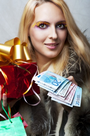 Portrait of glamour beauty woman with money (euro) and red christmas gift with gold ribbon photo