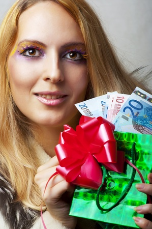 Portrait of glamour beauty woman with money (euro) and  christmas gift with red ribbon photo