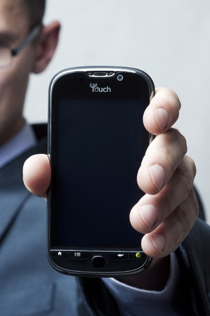 htc: Google phone My Touch 4g t-mobile (HTC Glacier) in male hand closeup Editorial