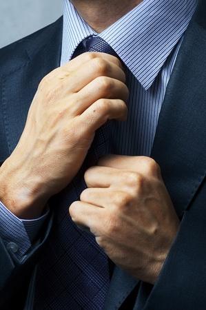 financial executive: executive adjusting tie closeup. Business man style
