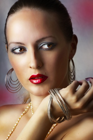 Fashion beauty portrait of sexy girl. Beautiful female face with bright glamour make-up. Woman and jewelry - silver earrings, bracelet closeup photo