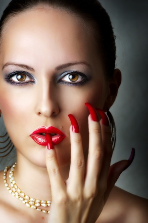 Fashion beauty portrait of young sexy model female face with glamour make-up for party - red glow lips and smoky eyes. Seductive woman with pearl necklace and stylish long nails photo
