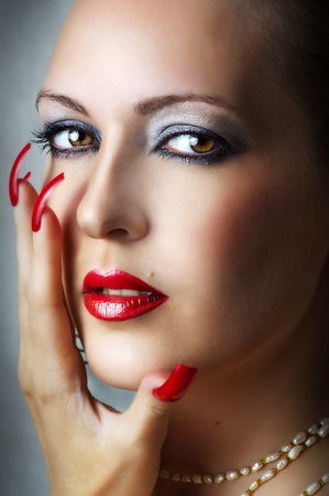 Fashion beauty portrait of young sexy model female face with glamour make-up for party - red glow lips and smoky eyes. Seductive woman with pearl necklace and stylish long nails Stock Photo - 11172294