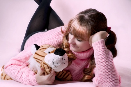 Beauty portrait of cute sexy brunette woman with soft toy. Female model lying on floor in the pink room. Little girl style photo