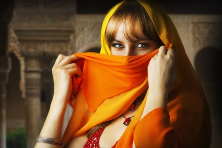 Belle brune yeux asian girl. Femme arabe � voile orange et jaune sur le visage, � l'Est costume traditionnel photo