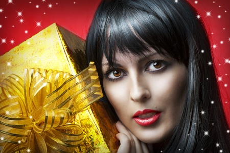 Glamour portrait of beauty woman with gold christmas gift box with ribbon on red background Stock Photo - 11172305