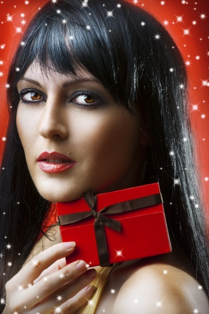 Glamour portrait of beauty woman with little red christmas gift box with brown ribbon on red background Stock Photo - 11172302