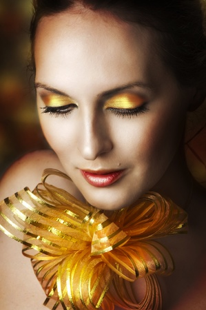 Glamour portrait of young fashion woman face with bright evening golden make up for party and gold ribbon on neck. Concept - make-up as christmas gift photo
