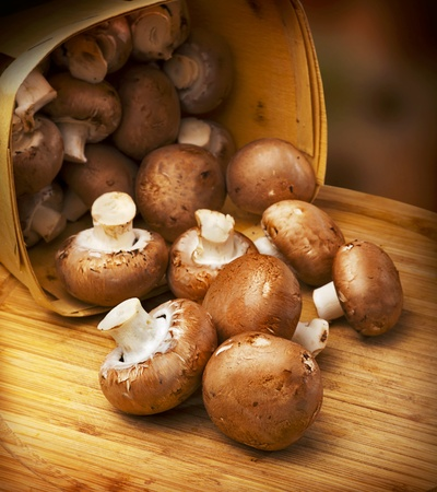 mushrooms: Champignon mushrooms with brown variety on wooden table (or board) scattered out of the basket
