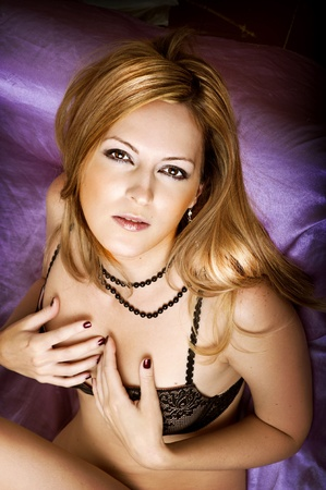 uñas largas: Retrato de la moda joven bella modelo femenino. Glamour mujer con el pelo largo acostado en la cama de seda en la ropa interior de encaje negro (bra)
