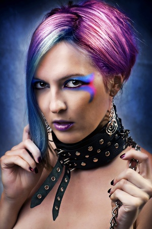 role model: Fashion underground punk look. Portrait of young woman with creative Brightly Colored hairstyle and multicolored make up and leather collar