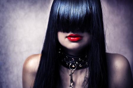 punos: Retrato de la moda joven bella modelo femenino. Glamour mujer con largo cabello negro y peinado sexy. La dama del collar de cuero con tachuelas en una cadena de metal