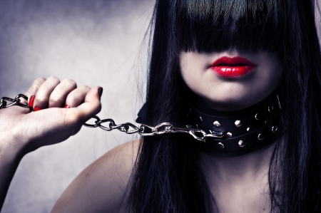 bdsm: Fashion portrait of young beautiful female model. Glamour woman with long black hair and sexy hairstyle. Lady with leather collar with studs on a metal chain in hand. Red make-up on lips and manicure Stock Photo