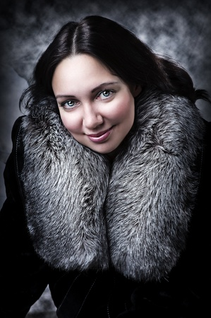 Fashion portrait of young adult  sexy woman - model in coat with fur collar photo