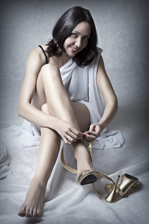 shoe model: Young sexy woman sitting on floor and wearing gold shoes